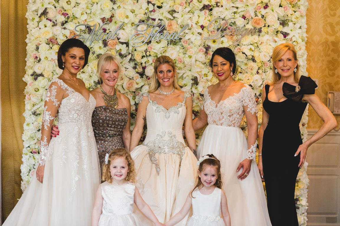 Van Cleve Bridal models in front of the Flower Wall by Nicol Floral Designs