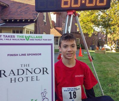 Collin of The Radnor Hotel Team at It Takes theVillage 5K Run Finish Line
